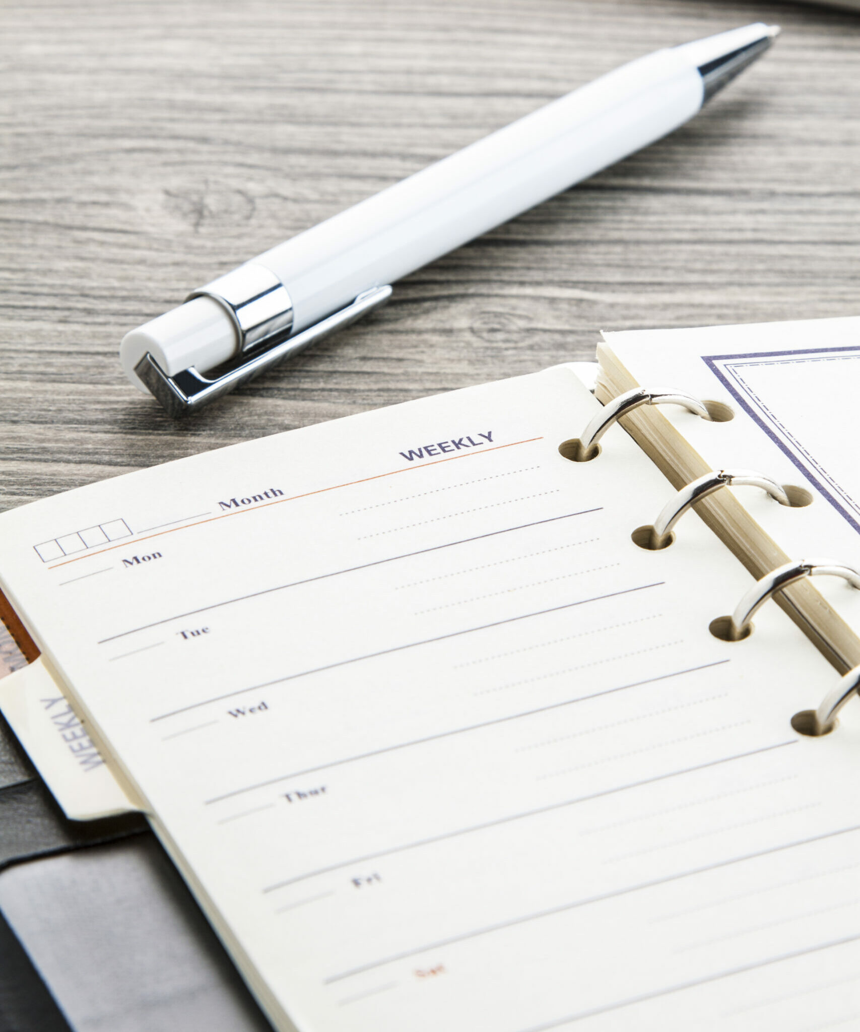 White ballpoint pen and leather weekly calendar on brown wooden table.
